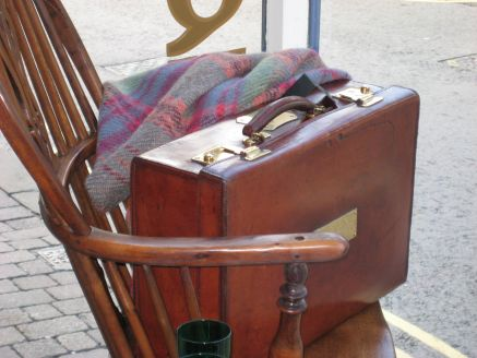 leather suitcase on 19thc windsor chair